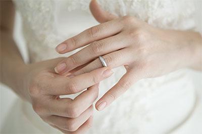 左手薬指に結婚指輪をはめる女性