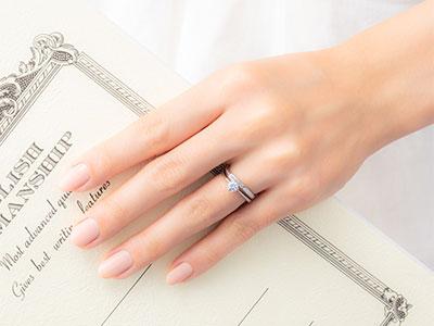 左手薬指に重ね着けされた結婚指輪と婚約指輪
