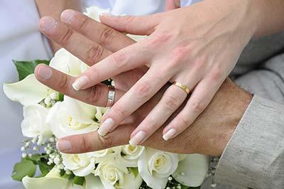 結婚指輪をつけているカップルの手